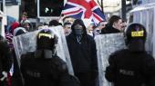 Politi iklædt kampuniform forsøger at holde en gruppe demonstrerende loyalister tilbage i den østlige del af Belfast i Nordirland den 12. januar 2013