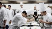 Der er få minutter til service. En kok og hans assistent lægger sidste hånd på anretningen, inden tallerkenerne sendes ud til dommerbordet.