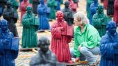 En kvinde nærstuderer én af 800 små figurer af Martin Luther på markedspladsen i Wittenberg – en installation af den tyske kunstner Ottmar Hörl.
