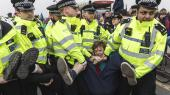 En demonstrant bliver båret væk under tirsdagens demonstration i London. Det er klimagruppen Extinction Rebellion der står bag demonstrationerne. Gruppen håber, at så mange som muligt bliver anholdt af politiet.