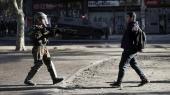 En demonstrant slår ud med armene foran et medlem af sikkerhedsstyrkerne under en protest mod den chilenske regering i Santiago den 18. december.