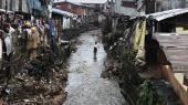 I slumkvarteret Susans Bay i Freetown vader en kvinde gennem det beskidte vand. Tusindvis af mennesker lever under kummerlige forhold uden vand og el, mens sygdomme og virus har let ved at sprede sig.