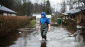 John Mikkelsen tramper igennem vandmasserne på sin terrasse. Han og hustruens gule murstenshus ligger som en ø omringet af vand til alle sider. De har haft oversvømmelser siden september.
