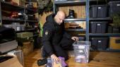 Jan Hansen, 45, i sit særlige depot. I kassen, han sidder med, er der blandt andet et kamera, et topografiskatlas og genopladelige batterier.