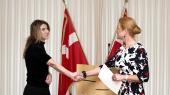 Kvinde udveksler håndtryk med tidligere udlændinge- og integrationsminister, Inger Støjberg, efter at have ansøgt om dansk statsborgerskab.