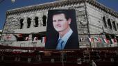 Plakater med Syriens præsident Bashar Al-Assad hænger stadig i Syriens hovedstad Damaskus. Men al-Assad sidder ikke så sikkert på magten som tidligere.