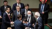 Jaroslaw Kaczynski (i midten med mundbind) er for kontroversiel til at tegne Polens regerende PiS-parti udadtil. Men da han skyr rampelyset, passer det ham efter sigende glimrende.