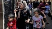 En palæstinensisk kvinde og hendes børn flygter fra de isralelske bombardementer i Gaza by.