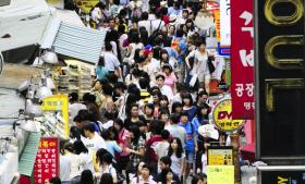 Sydkoreanere i Seouls Myeongdong-forretningskvarter. Det sydkoreanske økonomiske mirakel har ikke gavnet hele samfundet, idet landet har været meget optaget af beskæftigelse og produktion, men ikke i at opbygge en velfærdsstat, som fordelte den fælles skabte rigdom. Mange føler, at landet er lettet som en jumbojet af vækst, penge og velstand, men det kun blev de rige, der kom med om bord på turen.