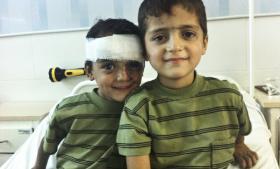 Bahaa (tv.) og Mulham kom på det syriske felthospital i begyndelsen af august, efter at de var blevet såret under Assads regeringsstyrkers angreb på deres by Kafranjed. Bahaa på fem fik bl.a. hjernerystelse og øjenskader, mens broderen Mulham på syv (th.) blev opereret i maven. I forgårs blev de begge, deres tre søskende og mor dræbt i et nyt angreb.