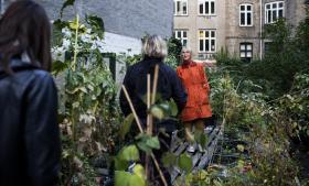 Vibeke Andersen i den orange frakke er med på rundvisningen Tour de Nørrebro, hvor interesserede byboere besøger bæredygtige initiativer i byen. Billedet her er taget hos TagTomat.