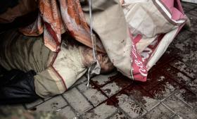 Et lig af en mand ligger på brolægningen i Kijevs centrum, efter at mellem 60 og 70 blev dræbt i går i kampe mellem antiterrorpoliti og oprørere, hvor begge lejre skød med skarpt. Rækker af lig lå både uden for to hoteller, uden for det centrale posthus og uden for en kirke, nær kamppladsen, for at de pårørende kunne identificere dem .