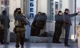 Russiske soldater med elefanthuer anholder ukrainske officerer på gaden i Simferopol på Krim i går.