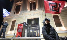 Et af Gyldent Daggrys partimedlemmer, Ilias Panagiotaros, taler her til en forsamling i Athen i februar i år. Ingen kan være i tvivl om, hvor partiet henter sit idémæssige ophav fra med det svastikaagtige-flagsymbol og den militaristiske fremtræden.