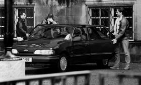 Blekingegade-kommissionen finder ingen grund til kritik af, at PET ikke af sig selv delte sin viden med Gladsaxe Politi, der i december 1985 skulle opklare et brutalt røveri i Herlev. Her ses et medlem af Blekingegadebanden dække ansigtet, da civilpoliti skal køre ham til Højesteret, hvor banden i maj 1991 fik sin endelige dom.