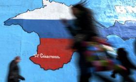 Fodgængere i Moskva passerer et maleri af Krimhalvøen i det russiske flags farver. Arkiv