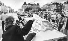 Demonstranter protesterer mod bilister, der trodser bilfri søndag. Oliekrisen med sin firedobling af oliepriserne i 1973 gives ofte som forklaring på, at udbredte forestillinger om 'den krisefri kapitalisme' blev en dårlig vittighed.