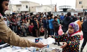 En IS-aktivist uddeler slik, sodavand og kiks til børnene på markedspladsen i Tel Abbyad i Raqqa-privinsen i det nordlige Syrien. Foto fra IS-site/Polfoto