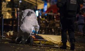 Politiets retsmedicinere og en politibetjent tilser en livløs krop, et af ofrene for det blodige angreb på spillestedet Bataclan i Paris, hvor mindst 100 personer blev dræbt.