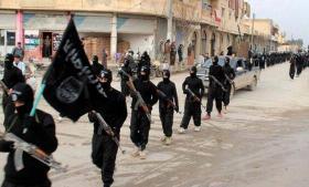 IS-folk går gennem den syriske by Raqqa.