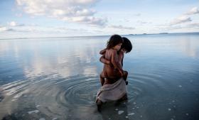En pige og hendes lillesøster leger i en lagune ved Kiribati, der en af verdens mest truede ønationer.
