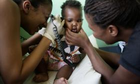 Seks måneder gamle Nomasonto bliver undersøgt af en af de medicinstuderende på hiv-forskningscentret på Universitetshospitalet i Soweto sammen med moderen Betty Dobe, der ligesom 10 procent af den sydafrikanske befolkning er hiv-smittede.