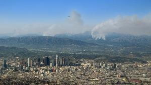 En gigantisk hvid røgsky lå tirsdag over Los Angeles, mens omfattende skovbrande spredte sig over store områder omkring storbyen, og myndighederne advarer om, at det kan tage uger at bringe flammerne under kontrol.
