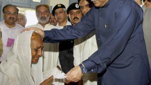 Pakistans præsident, Asif Ali Zardari, (med hvid hue) kom ikke hjem fra sin Europarejse i katastrofens første 12 dage. Da han endelig begav sig til de oversvømmede områder, blev han mødt af kritik. Her giver han en hjemløs kvinde en symbolsk sølle check under sit besøg i Sukkur, hvor titusinder er ramt af oversvømmelserne.