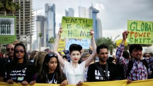 Klimaforkæmpere demonstrerer på gaden ved COP18 i Doha, Qatar. Demonstranterne vil have de store, miljøforurenede stater til at tage ansvar for miljøet.