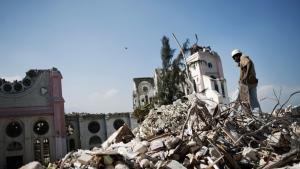 En mand kigger efter brugbare rester i ruinerne af huse foran den sammenstyrtede katedral i Port-au-Princes centrum i ugen efter jordskælvet den 12. januar 2010.