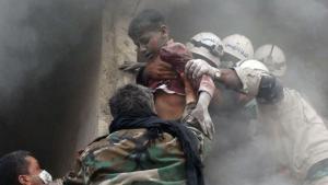 En såret syrisk dreng hjælpes ud af en bygning i Aleppo, der braste sammen, efter den blev ramt af en såkaldt tøndebombe fyldt med søm og sprængstof  smidt ned fra regeringshærens helikoptere.