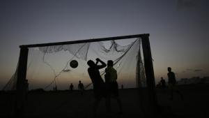 Unge mænd i Bahrain spiller fodbold i tusmørket. Den bahrainske kandidat til præsidentembedet i FIFA, Sheikh Salman, møder kritik fra flere sider.
