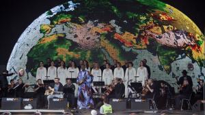 Damon Albarn (med guitaren på øverste billede) spillede en relativt diskret rolle ved åbningskoncerten på Roskilde Festivals Orange Scene. I stedet var Raed Jazbeh (nederst til højre) og The Orchestra of Syrian Musicians samlet fra alle verdenshjørner i en (lidt for) politisk korrekt koncert.