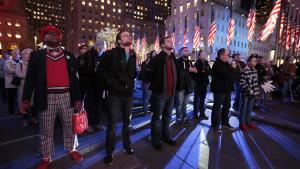 Howard Nizebeth, til venstre, ser nyhederne rulle ind på tv-skærmen sammen med andre amerikanere på Rockefeller Center i New York.