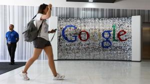 A visitor passes a sign featuring Google Inc.'s logo inside their new U.K. headquarters at Six St Pancras Square in London, U.K., on Tuesday, June 21, 2016. The owner of the world's largest search engine built its new U.K. headquarters on 2.4 acres (1 hectare) of land that's part of a larger development by King's Cross Central LP near the Eurostar rail link to mainland Europe. Photographer: Chris Ratcliffe/Bloomberg