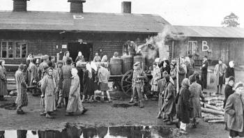 Britiske soldater uddeler mad til befriede fanger i Bergen-Belsen i 1945. Var Holocaust en unik tysk begivenhed – eller en del af et større civilisatorisk udryddelseforløb? Det handler den nye tyske historikerstrid om.
