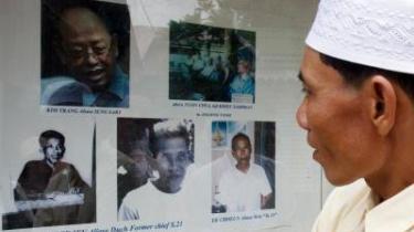 En gæst på Phnom Penhs folkemordsmuseum kigger på et billede af torturbødlen. Khang Guev Eav (i midten nederst) som nu er blevet stillet for retten.