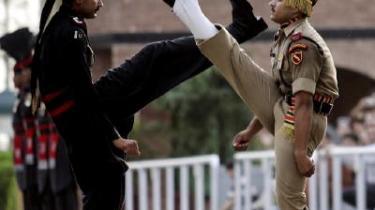 En indisk (th.) og pakistansk (tv.) grænsevagt puster sig op ved landenes fælles grænsekontrol