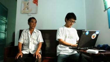 Den 26-årige blogger Zhou Shuguang sidder med den computer, der er hans redskab til at angribe Mao Zedongs arvtagere. Faren, det 66-årige partimedlem, sidder i stuen under en kalender med et billede af netop formanden, som han stadig nærer sentimentale følelser for.