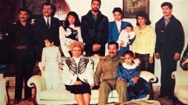 Familieportræt. På dette billede fra 1990 troner Saddam Hussein i sofaen med sine hustru og to børnebørn. I bageste række fra venstre ses svigersønnerne Hussein Kamel og Saddam Kamel (begge blev senere myrdet efter hjemkomst fra eksil), Saddam Kamels kone Rana, Saddams ældste søn Udai, (dræbt i en amerikansk kommandoaktion), Saddams datter Raghad (luksuseksil i Jordan) med Saddams første barnebarn af hankøn, en unavngiven kvinde og endelig Saddams yngste søn Qusai (dræbt i en amerikansk kommandoaktion sammen med broderen Udai).
