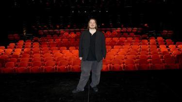 Den kommende Hamlet, Nicolas Bro, med ryggen mod den mørke scenehule med de røde stole.