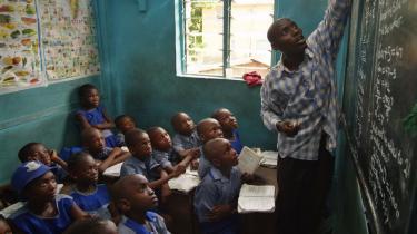 Videbegærlige elever lytter til en lærer, der gennemgår en tekst ved tavlen. Billedet er fra en skole, der ikke ikke noget med ADPP og Tvind at gøre.