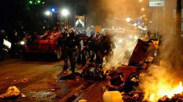 Kampklædt politi bevogter en bulldozer, mens den arbejder med at fjerne en brændende affaldsdynge i Napoli tirsdag aften. Storbyen er midt i en skraldekrise, som bunder i de kriminelle organisationers kontrol med byens renovation.