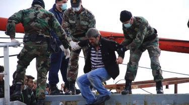Græske soldater fra kystvagten gelejder en mellemøstlig flygtning fra borde fra et skib fyldt med flygtninge på vej mod den græske kyst i november 2007.