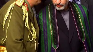 Generalstabschef Abdul Rashid Dostum (tv.) i samtale med Afghanistans præsident, Hamid Karzai (2005). Det er kendt, at Dostum, da han styrede en håndfuld nordafghanske provinser, begik adskillige forbrydelser over for politiske modstandere. Det nuværende styre i Afghanistan med Karzai i spidsen ser dog ingen udvej for at slippe af med Dostum: Det vil bringe uro i en ellers stabil del af Afghanistan, og der er ingen umiddelbar afløser for ham.