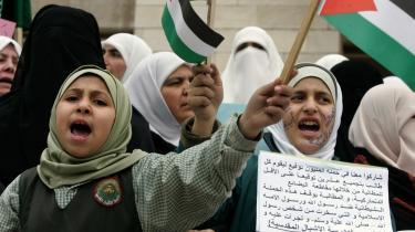 Jordanske skolepiger råber anti-danske slogans uden for den danske ambassade i hovedstaden Amman. Pigen til højre holder et skilt, hvor der på arabisk står -tag del i boykotten af danske varer-.