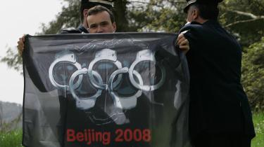 Demonstranter blev i går ført væk af politi efter en kortvarig forstyrrelse af en ceremoni i Olympia i Grækenland, hvor solens stråler tændte den olympiske fakkel.