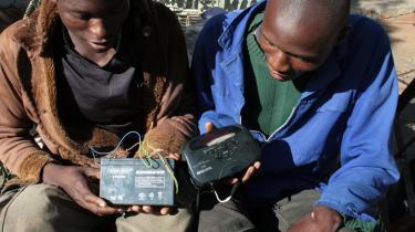 Under en afbrydelse af strømforsyningen i Bulawayo tyr disse to unge mænd til batteriradioen for at høre nyt om udfaldet af lørdagens valg. Man må håbe for dem, at der er godt med strøm på batterierne, for resultaterne kommer kun drypvis og uendeligt langsomt.