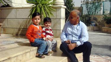 Palæstinenseren Fadhallah sidder med et par børnebørn foran sit jordanske hus i en forstad til Amman.