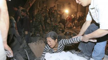 En overlevende kvinde reddes ud fra en sammenstyrtet skole i Dujiangyan i Sichuan-provinsen. Omkring 900 teenagere blev begravet under murbrokker fra den treetagers bygning.